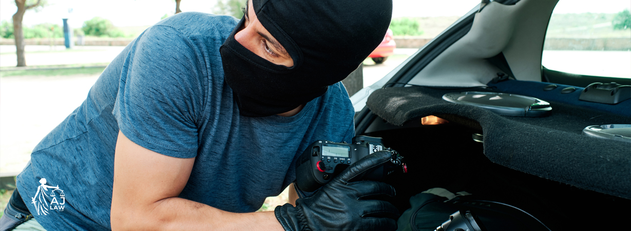 thief-with-mask-stealing-photography-equipment-lenses-from-car-criminal-lawyer-aj-law-llp